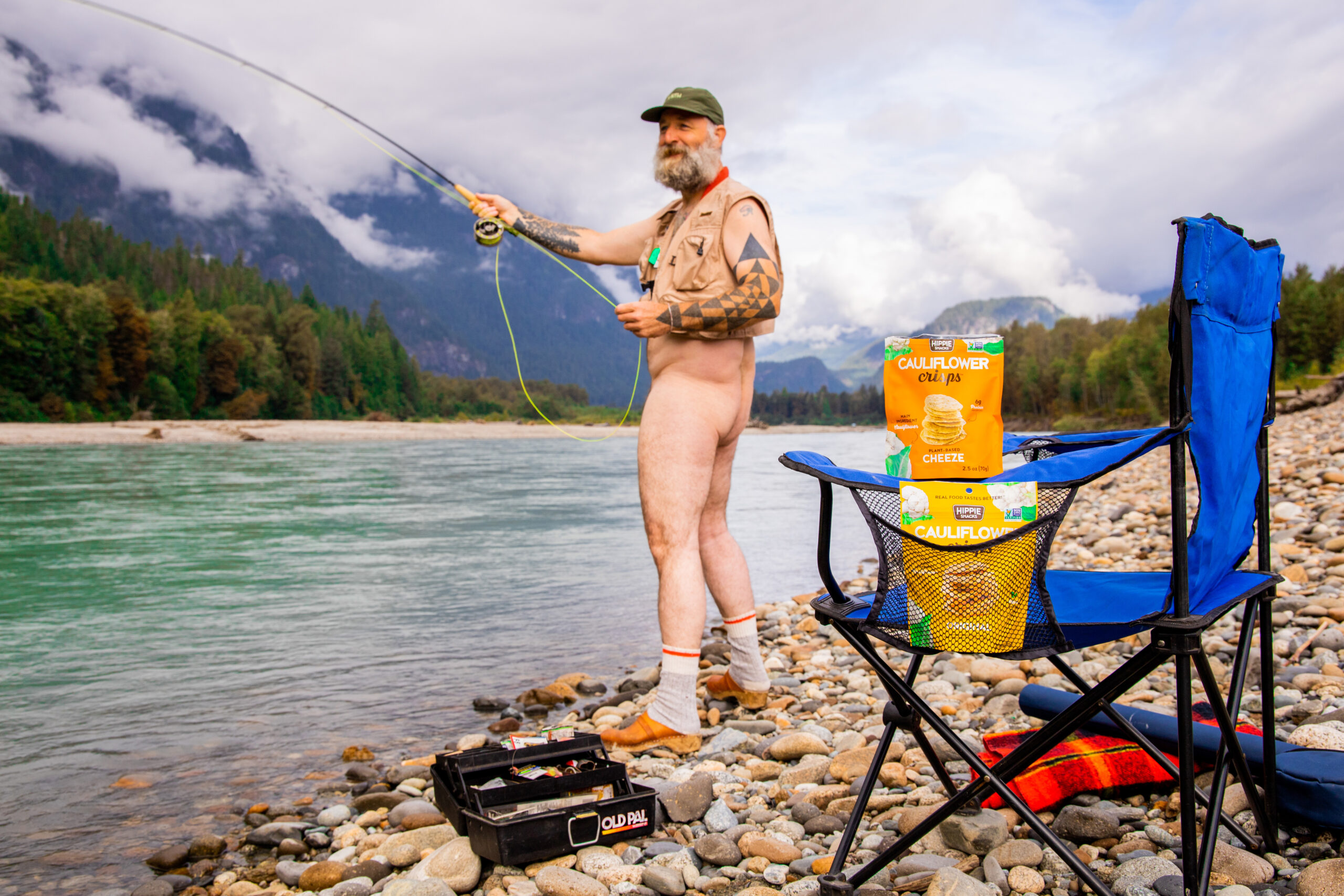 Naked man fishing beside a river with Hippie Snacks