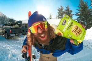 Man holding Hippie Snacks up to the camera with his skis and pit viper sunglasses